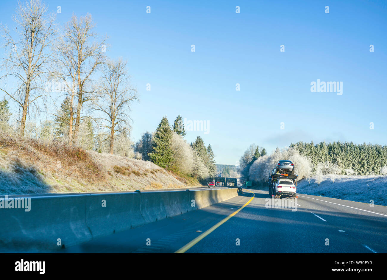 Big rig commercial grade professional car hauler semi truck transporting cars on the special two level semi trailer moving on the straight highway wit Stock Photo