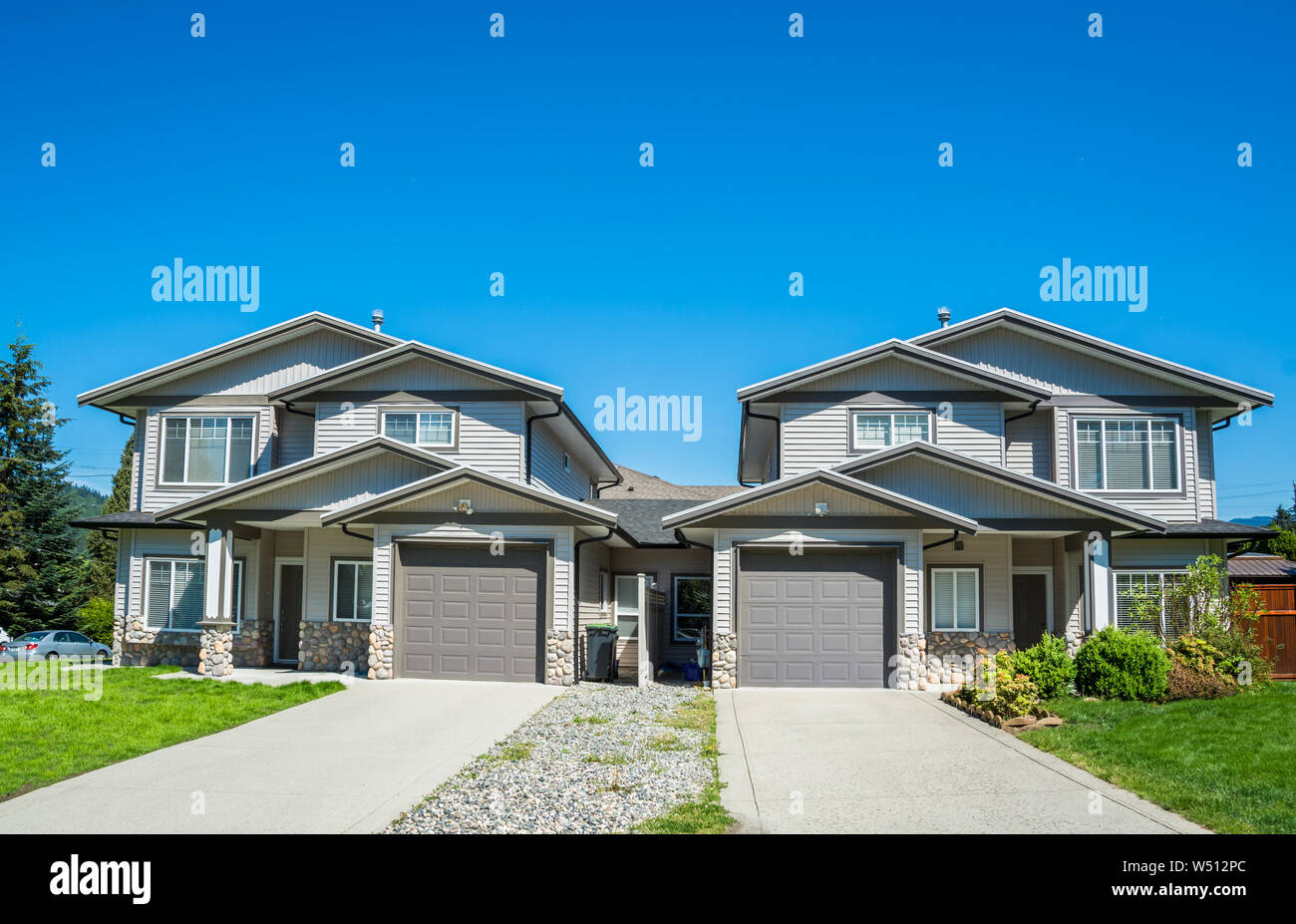Residential duplex building with concrete drive ways and green lawns in front Stock Photo