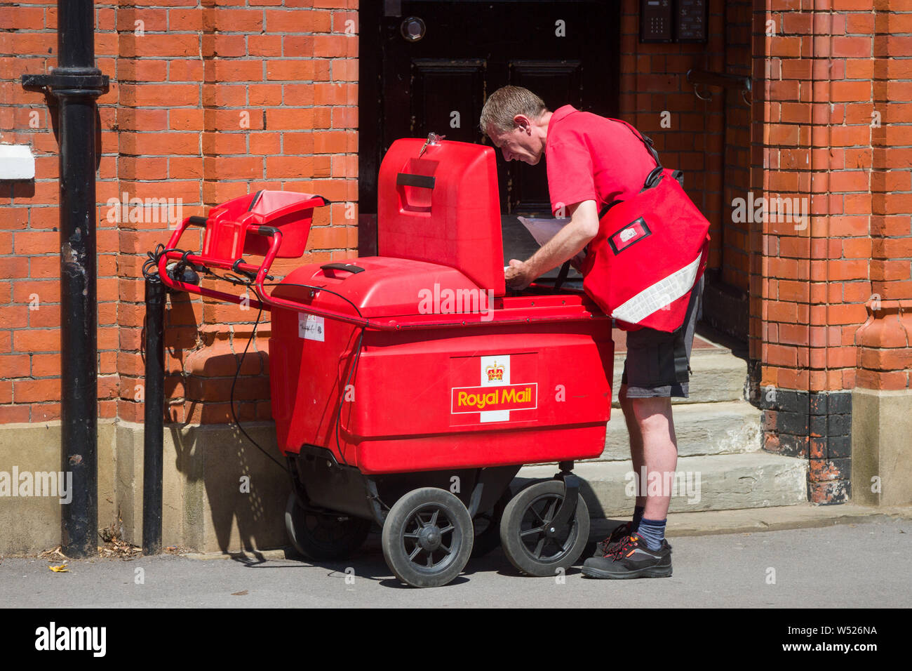 a-postman-collects-mail-for-delivery-from-an-electric-postal-round-royal-mail-delivery-trolley-or-hand-cart-W526NA.jpg?profile=RESIZE_400x