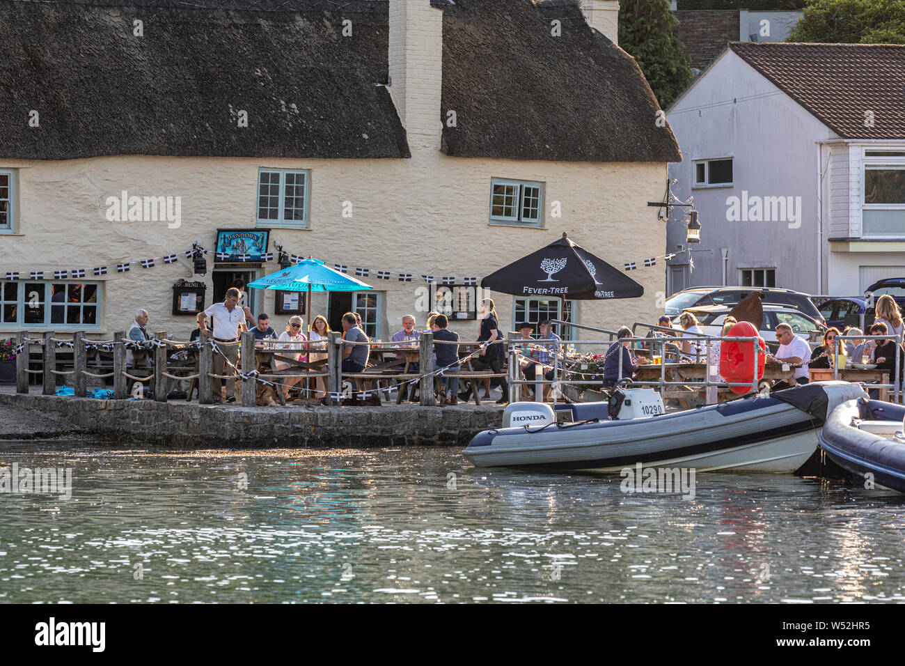 Customers drink outside the Pandora Inn at high tide in Restronguet Creek Stock Photo