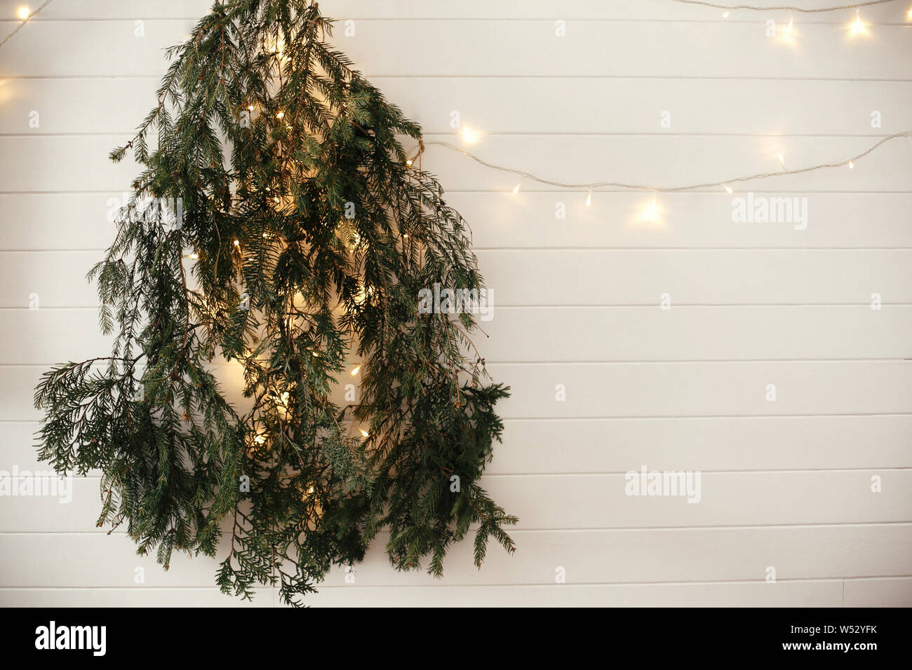 Stylish Modern Christmas Tree Made Of Fir Branches Hanging On White Wall With Festive Garland Light Eco Zero Waste Decoration Of A Room For Christma Stock Photo Alamy