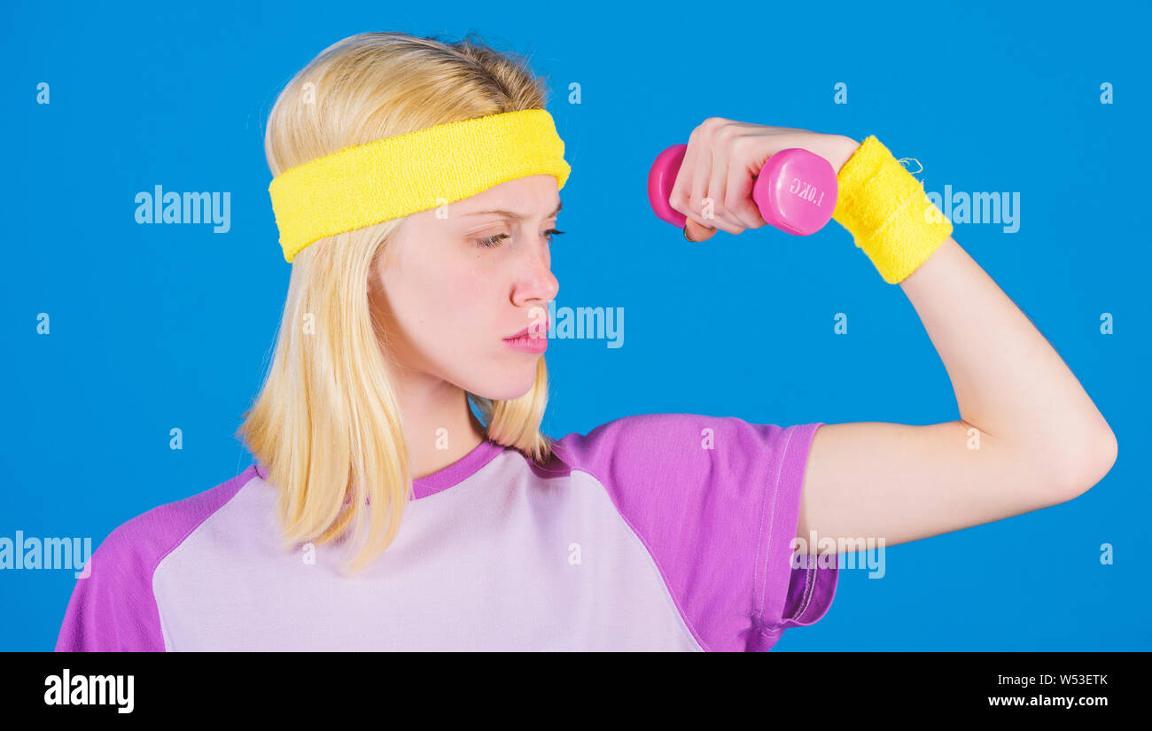 Ultimate upper body workout for women. Fitness concept. Girl exercising with dumbbell. Fitness instructor hold little dumbbell blue background. How to get toned physique. Beginner dumbbell exercises. Stock Photo