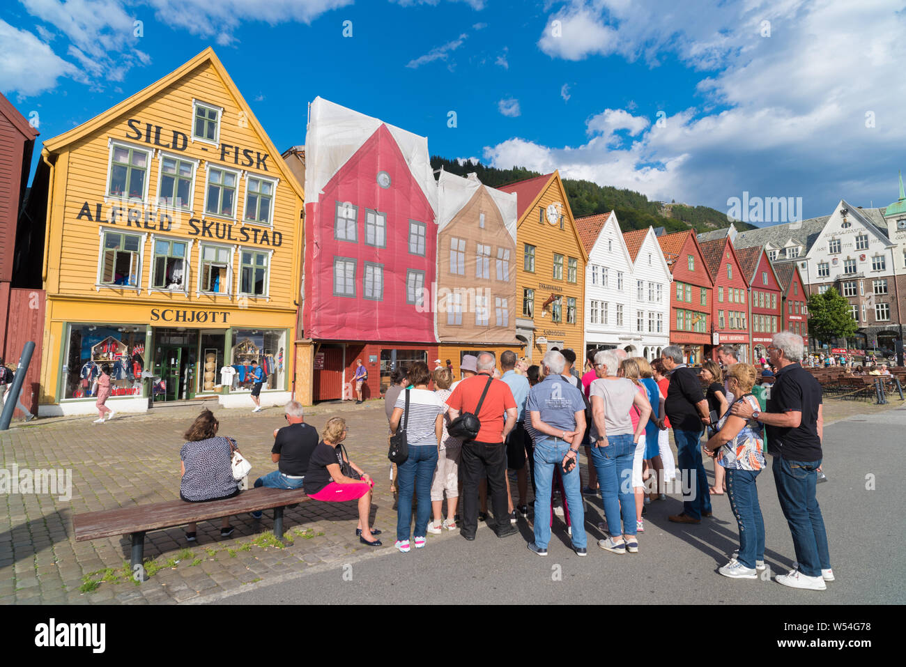 BERGEN, NORWAY - JULY 28, 2018: Tourists in front of the historical buildings in Bryggen- Hanseatic wharf. Bryggen has been on the UNESCO World Herita Stock Photo