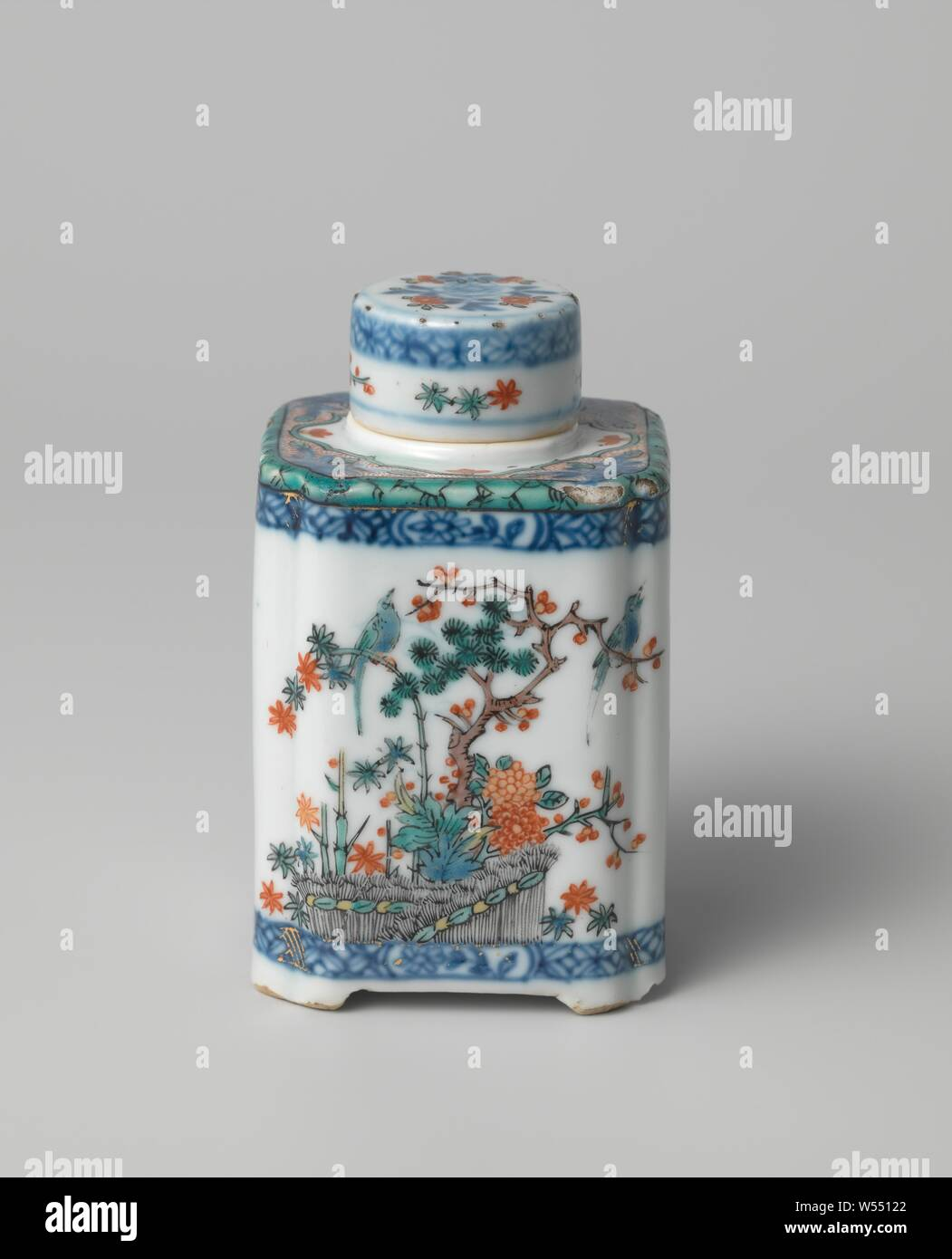 Square tea caddy with flowering plants, birds, butterflies and diaper patterns, Square tea caddy of porcelain with squeezed corners and on four feet, painted in underglaze blue and on the glaze blue, red, green, yellow, black and gold. In China on the wall in underglaze blue decorated with flower sprays and two bands with napkin work interrupted by a flower branch in a cartouche, the shoulder with four flower sprays. Decorated in Europe in enamel with a butterfly on two sides above a flowering plant and on two sides the 'three friends of winter' (pine, prunus, bamboo) and birds tied behind Stock Photo