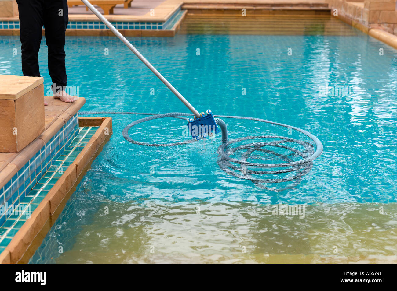 Worker cleaning swimming pool with vacuum tube in the ...