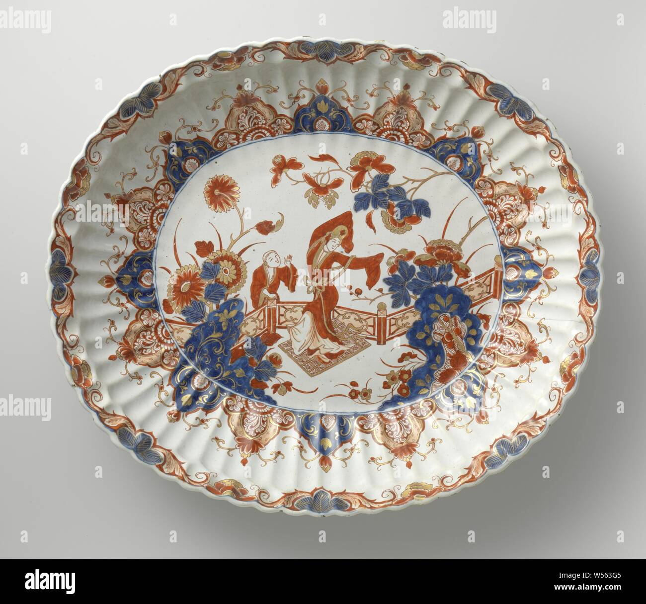 Ewer and basin Basin, Dish of faience. Multicolored painted with figures in a garden and lambrequin edge, Chinese (other cultural aspects), De Grieksche A, Delft, c. 1701 - c. 1722, h 34.8 cm × w 40.5 cm × d 7.4 cm Stock Photo