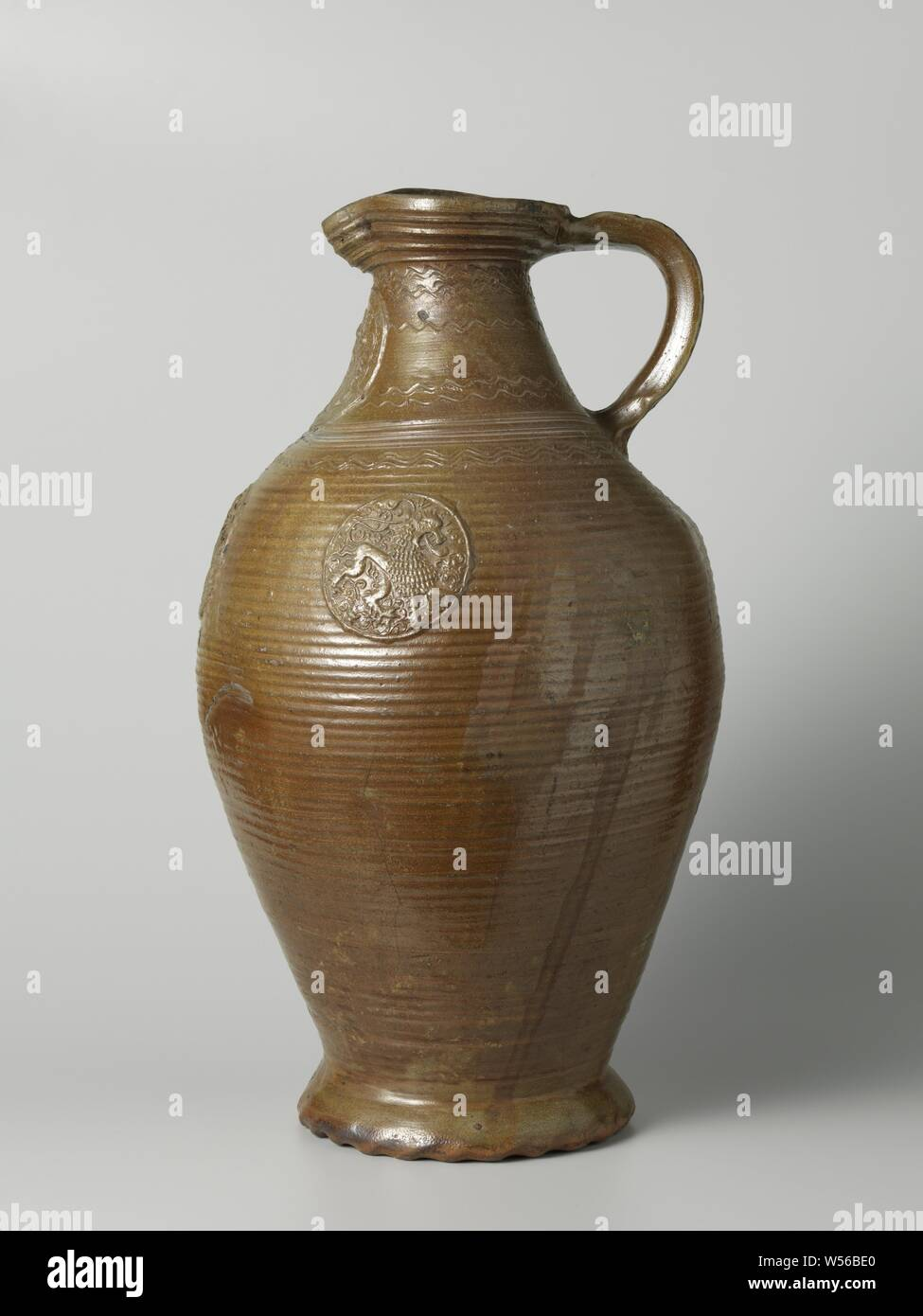 Storrage vessel with a coat of arms and lions, Stock jug of stoneware on wavy feet with an egg-shaped body and wide neck with a pinched spout. The C-shaped ear is attached to the neck and shoulder. Profiles on the neck and shoulder. Covered with a brown engobe. The jug is decorated with rotating rings. On the neck in relief a printed and imposed medallion with a weapon and the edge lettering 'I.WILHELMVS.VO.REIFENBERG M.I.ANNA VOM BATEMBORG.1604'. The belly with three smaller medallions with a lion, the brand 'W.E.' and the date '1600'. On the neck and shoulder bands with incised, wavy lines Stock Photo