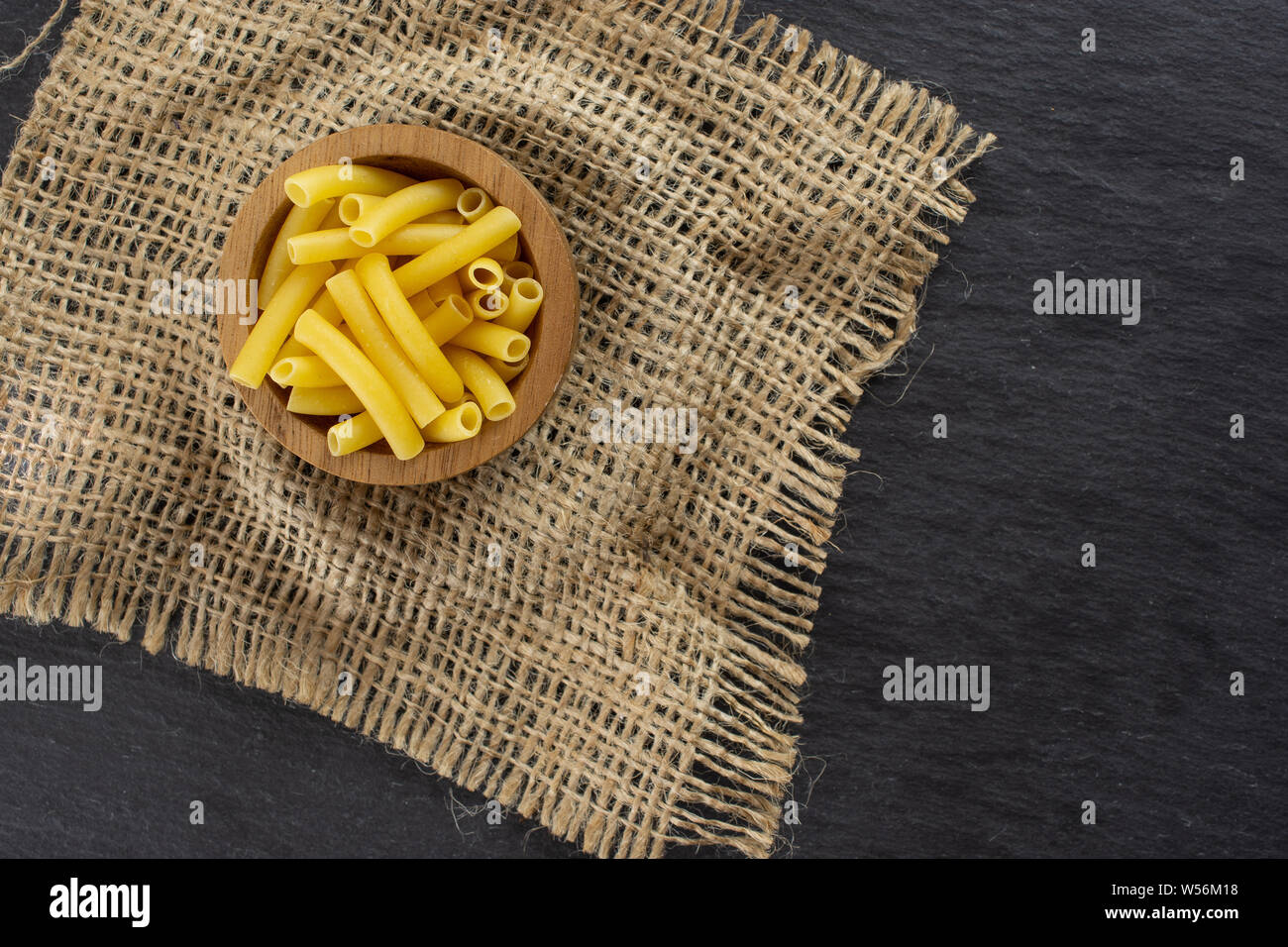 Lot of whole raw pasta macaroni in a wooden bowl with jute cloth flatlay on grey stone Stock Photo