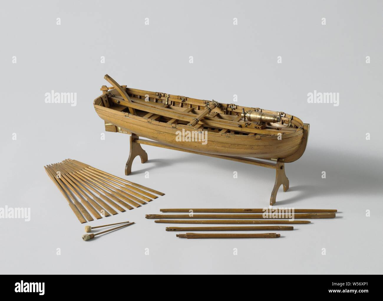 Model of an Armed Longboat, Truss model with round wood on a stand. Smooth-edged double-belted barkas, round truss with flat sheer and flat mirror, a forecourt, five diets and rails and an open cabin with side dents. The prow is coppered and has a disk. Three-part frames. Simple rudder with a tiller that fits over the rudder king. The rig consists of a large mast with ra for a bucket sail and a grape mast with a parrot pole and whip. The barkas is armed with a carronade on a loose carriage, which extends from the front to the stern, and is provided with loading equipment. On separate parts Stock Photo