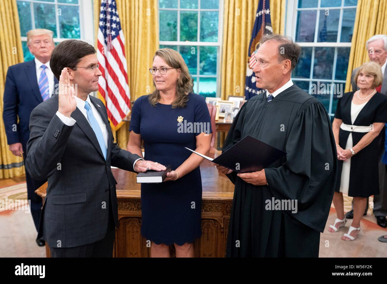 U.S Secretary of Defense Mark Esper, left, takes the oath of office from Supreme Court Associate Justice Samuel Alito as his wife Leah Lacy, center, looks on, during a ceremony in the Oval Office of the White House July 23, 2019 in Washington, DC. Stock Photo