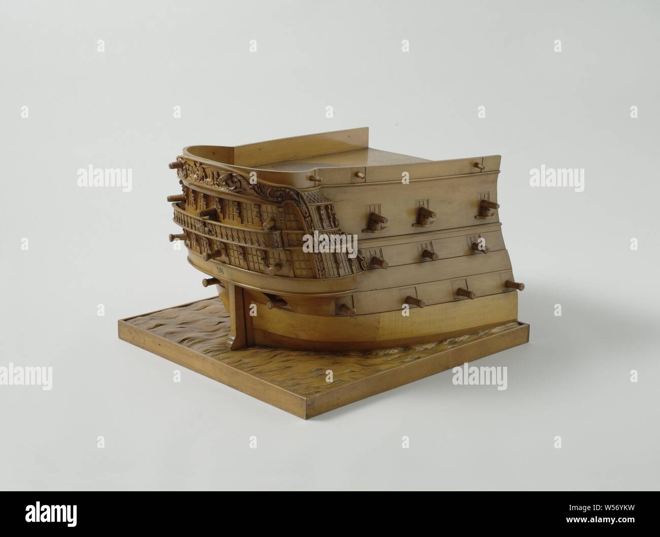 Model of the Stern of an 84-Gun Ship of the Line, Waterline model of the stern of a line ship of 84 pieces. Waterline model of the external appearance of a stern on a floorboard in which waves are carved in relief. Round stern with two-storey wulf and fence, elaborately decorated with trophies, mythological figures and accolades, and with side galleries. The western corridor on the top floor is decorated with the Rijkswapen and is supported by volute-shaped knees. Above the fence a Neptune surrounded by tritons. Triangular hemp hole in the wulf. Four decks are indicated by gates with fire Stock Photo