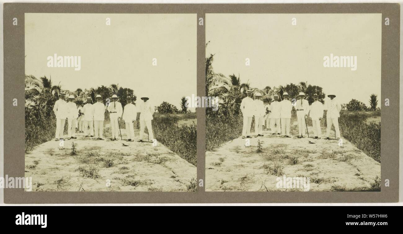 Ned. Indie, Borneo, seven whites with a native servant in the background standing on a country road or flat piece of land, anonymous, 1910 - 1930 Stock Photo