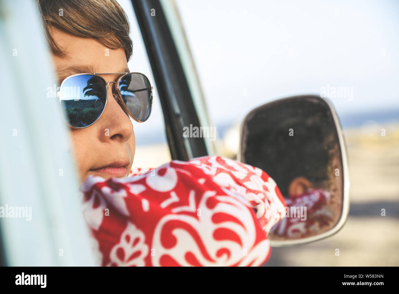 Handsome teenage boy with sunglasses posing charming out the window of a vintage van dressed as a flower hippie child. Concept of freedom and lighthea Stock Photo