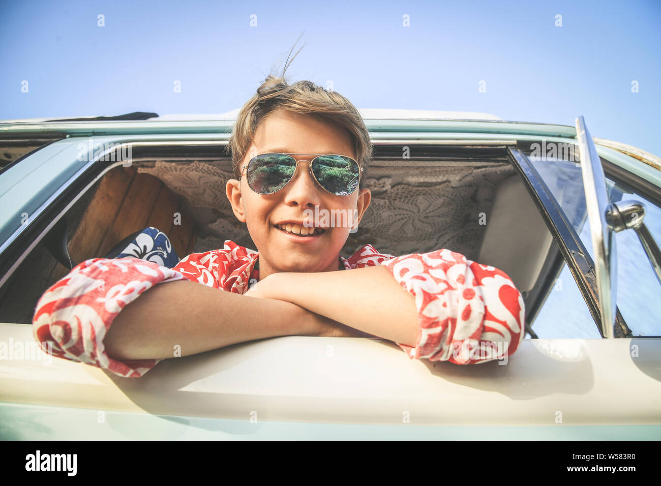 Bottom view of handsome boy with sunglasses posing charming out the window of the vintage van dressed as flower hippie child Concept of freedom and li Stock Photo