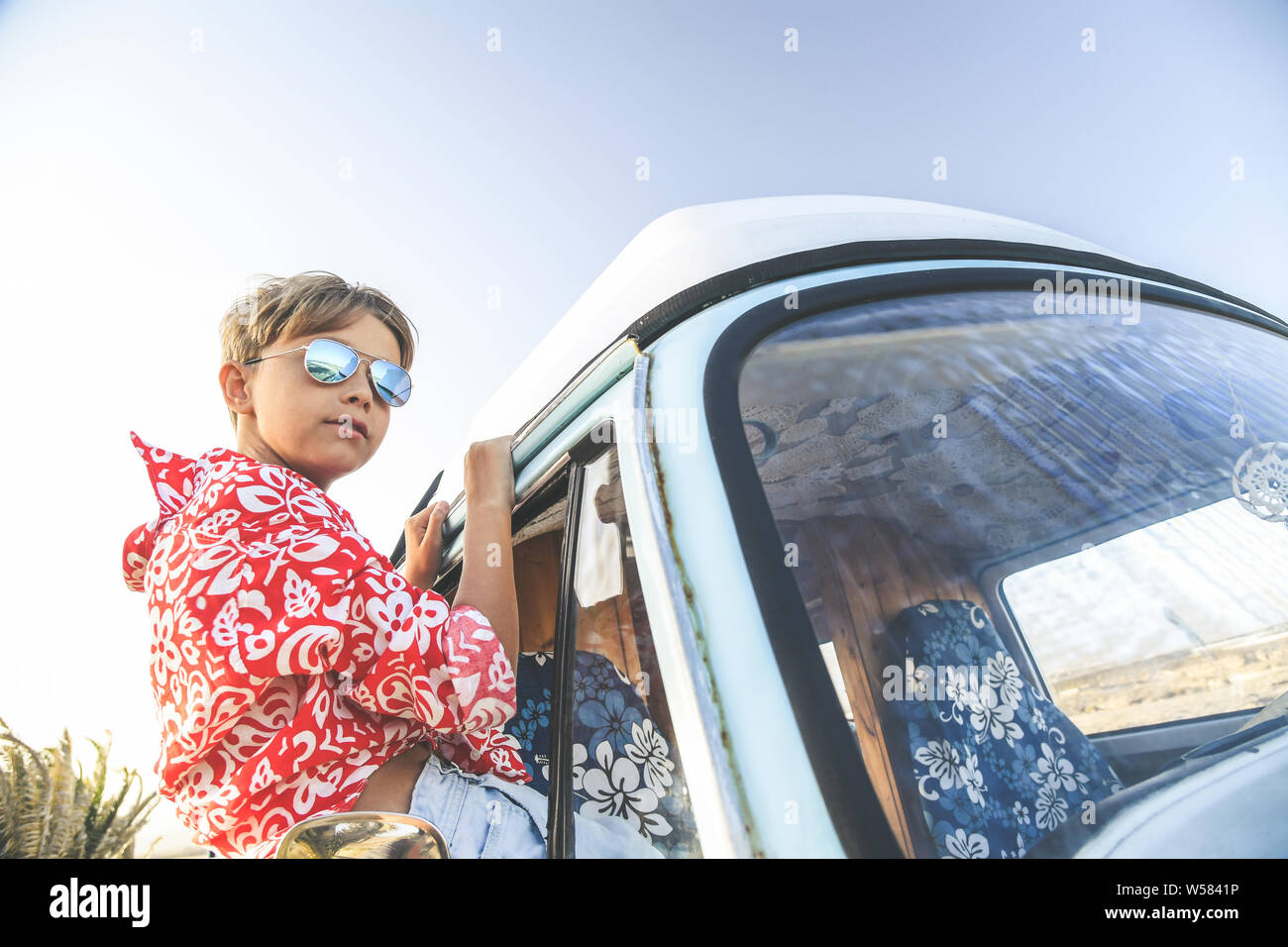 Handsome teenage boy with sunglasses posing charming out the window of the vintage van dressed as a flower child, hippie. Concept of freedom and light Stock Photo