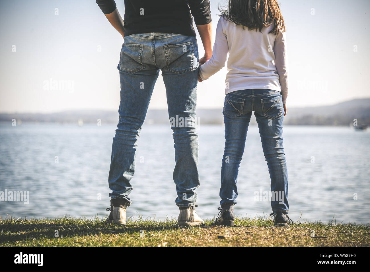 Father and daughter holding hands near the sea. two people standing on the seashore in a beautiful sunny day. Dad and little girl looking at horizon. Stock Photo