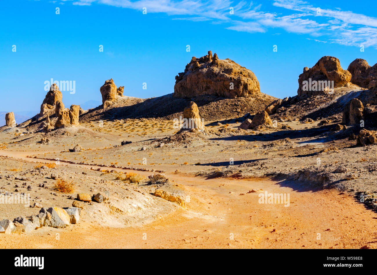 Reddish brown dirt road leading towards desert rock formations in the morning sunlight under bright blue skies. Stock Photo