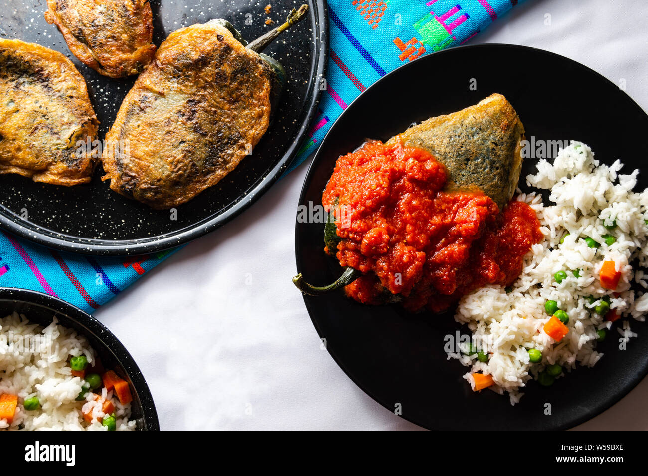 Mexican stuffed chiles (Chiles Rellenos), poblano chiles filled with cheese and coated with a light batter. Served with rice and red tomato sauce Stock Photo