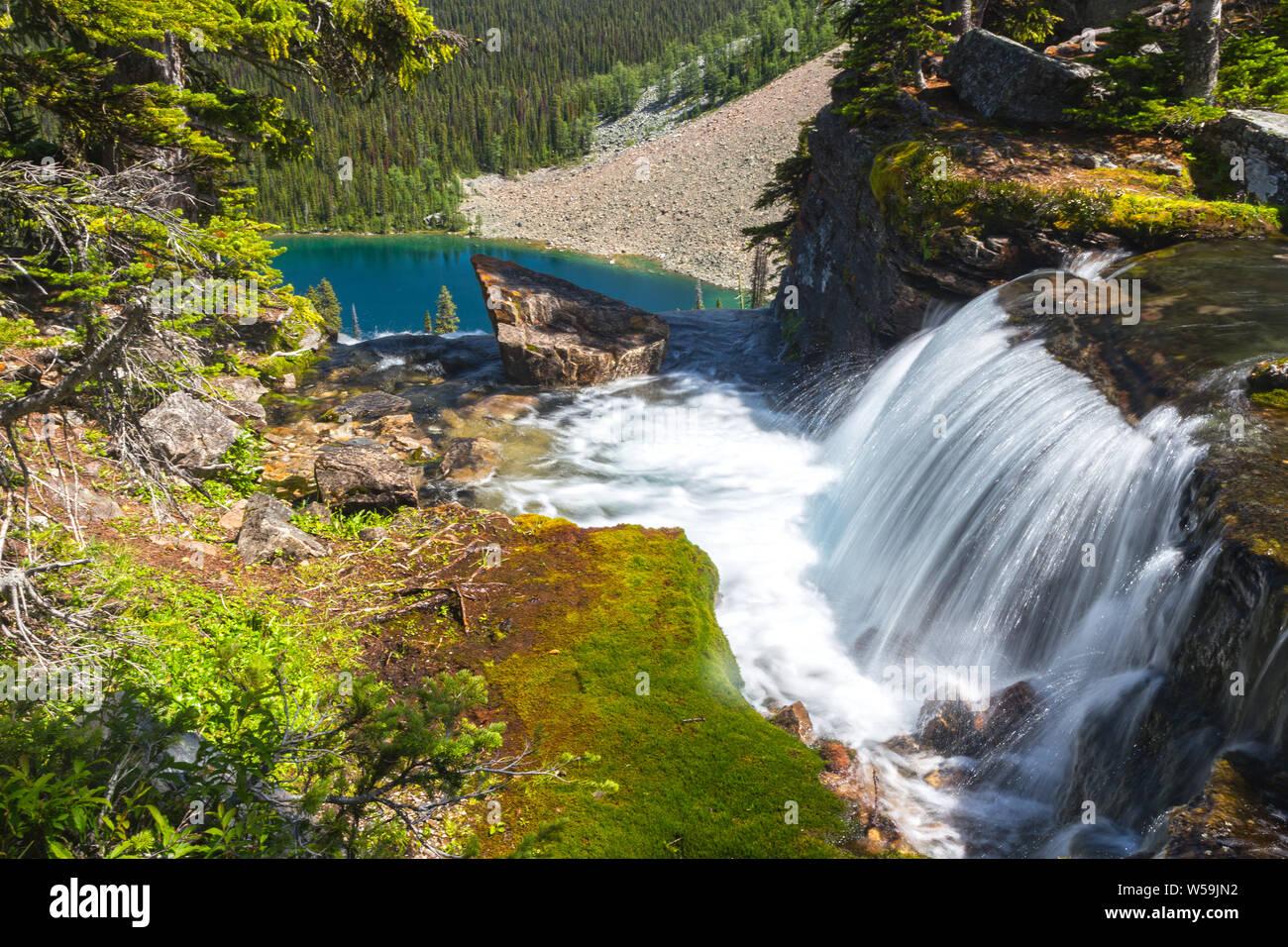 Beautiful Cascading Waterfall, Green Moss and Blue Egypt Lake Landscape Scenery Banff National Park Canadian Rocky Mountains Stock Photo