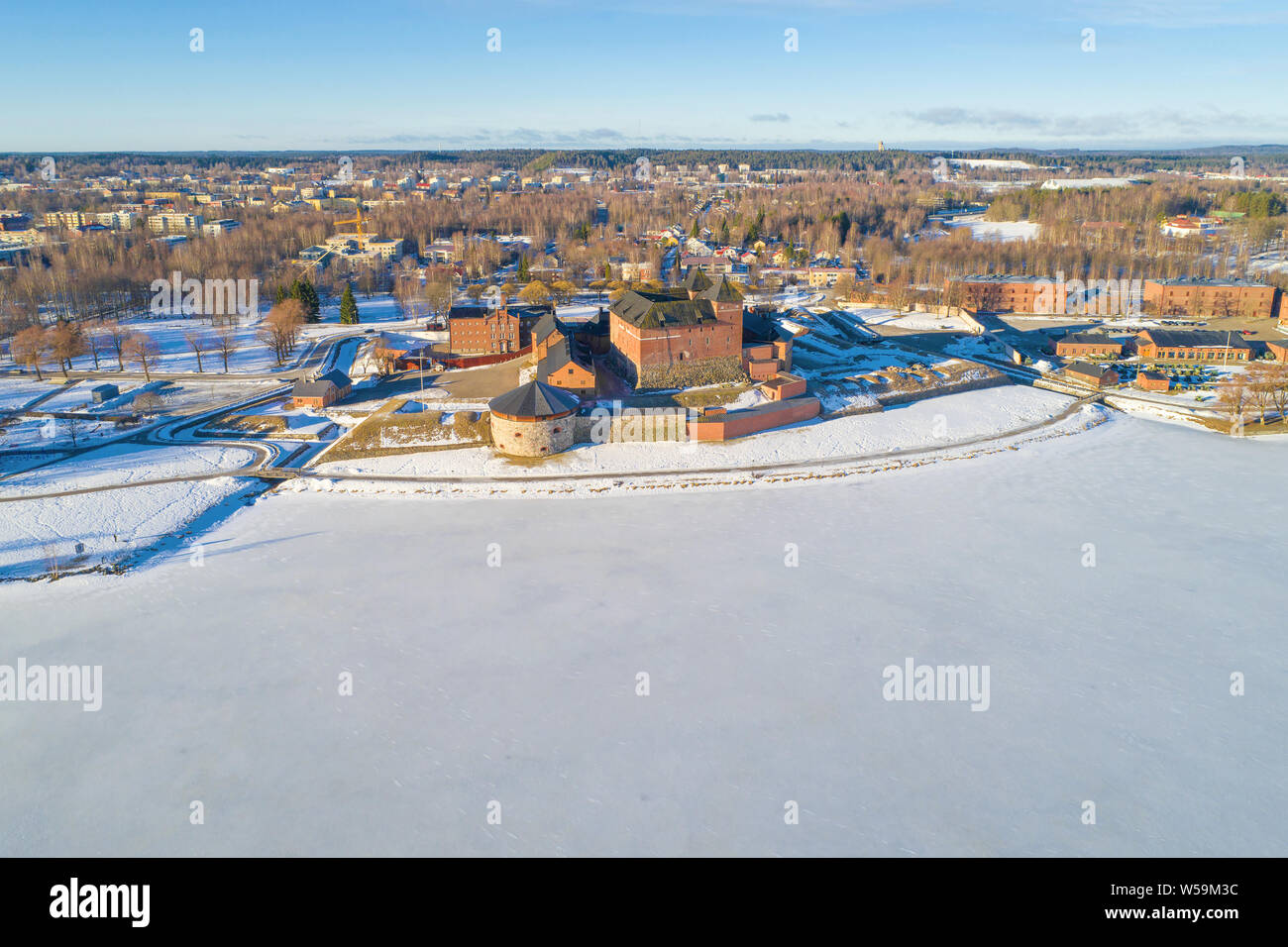 View of the frozen Vanajavesi  lake and the ancient fortress off Hameenlinna on a sunny March morning (aerial survey). Finland Stock Photo