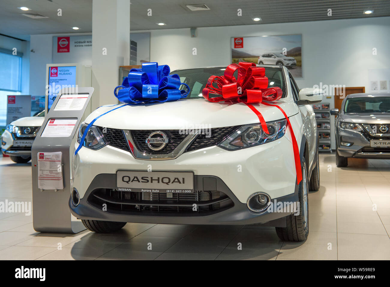 ST. PETERSBURG, RUSSIA - JULY 09, 2019: The sold car Nissan Qashqai (2019) with two bows of red and blue color in car showroom Stock Photo