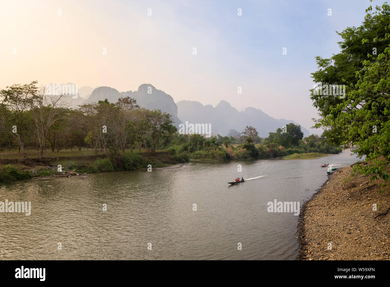 View of two small boats on the Nam Song River and limestone karst mountains in Vang Vieng, Laos. Stock Photo