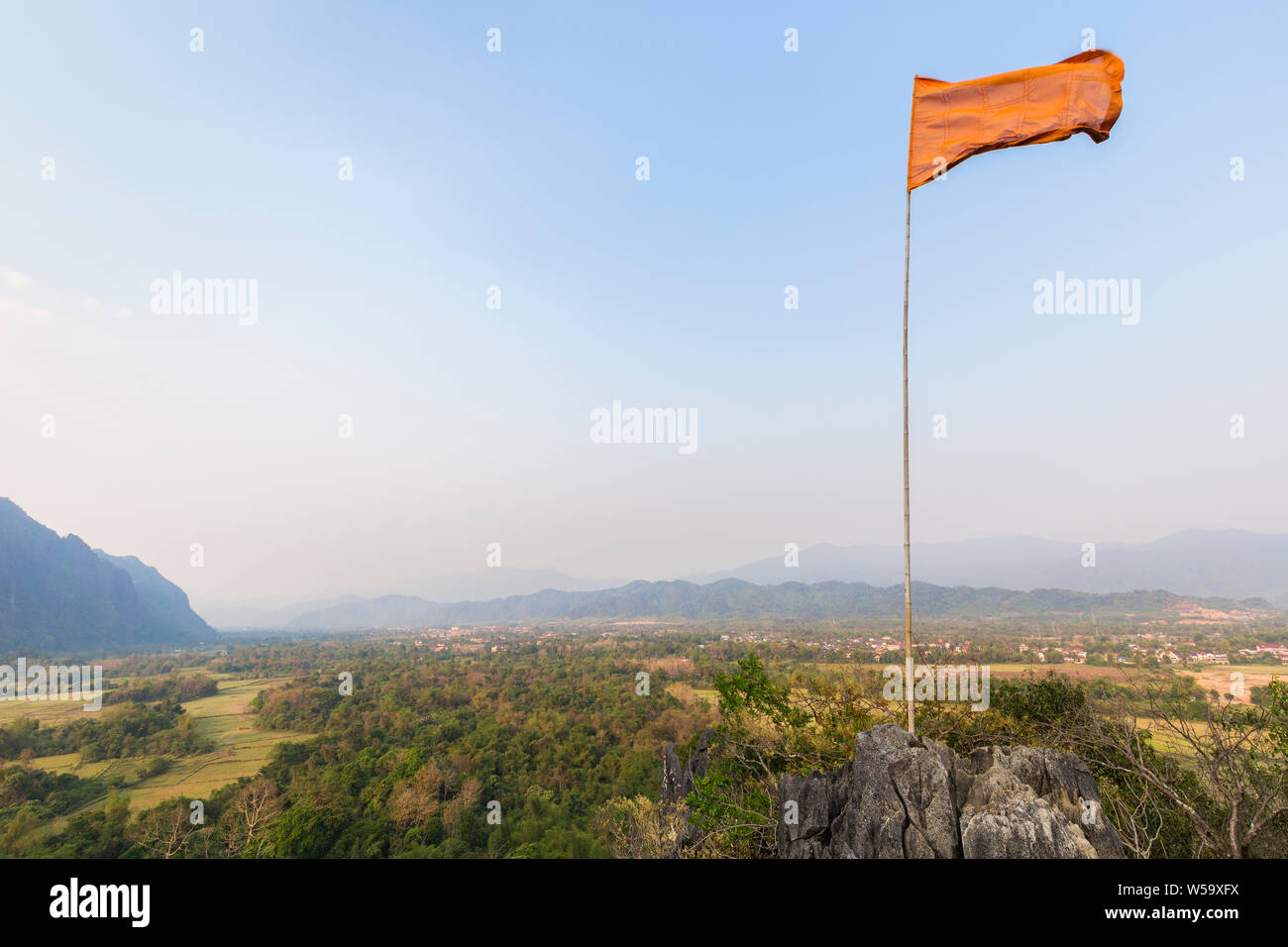 Flag fluttering atop the Pha Poak hill. Beautiful view of fields and mountains from above near Vang Vieng, Vientiane Province, Laos, on a sunny day. Stock Photo