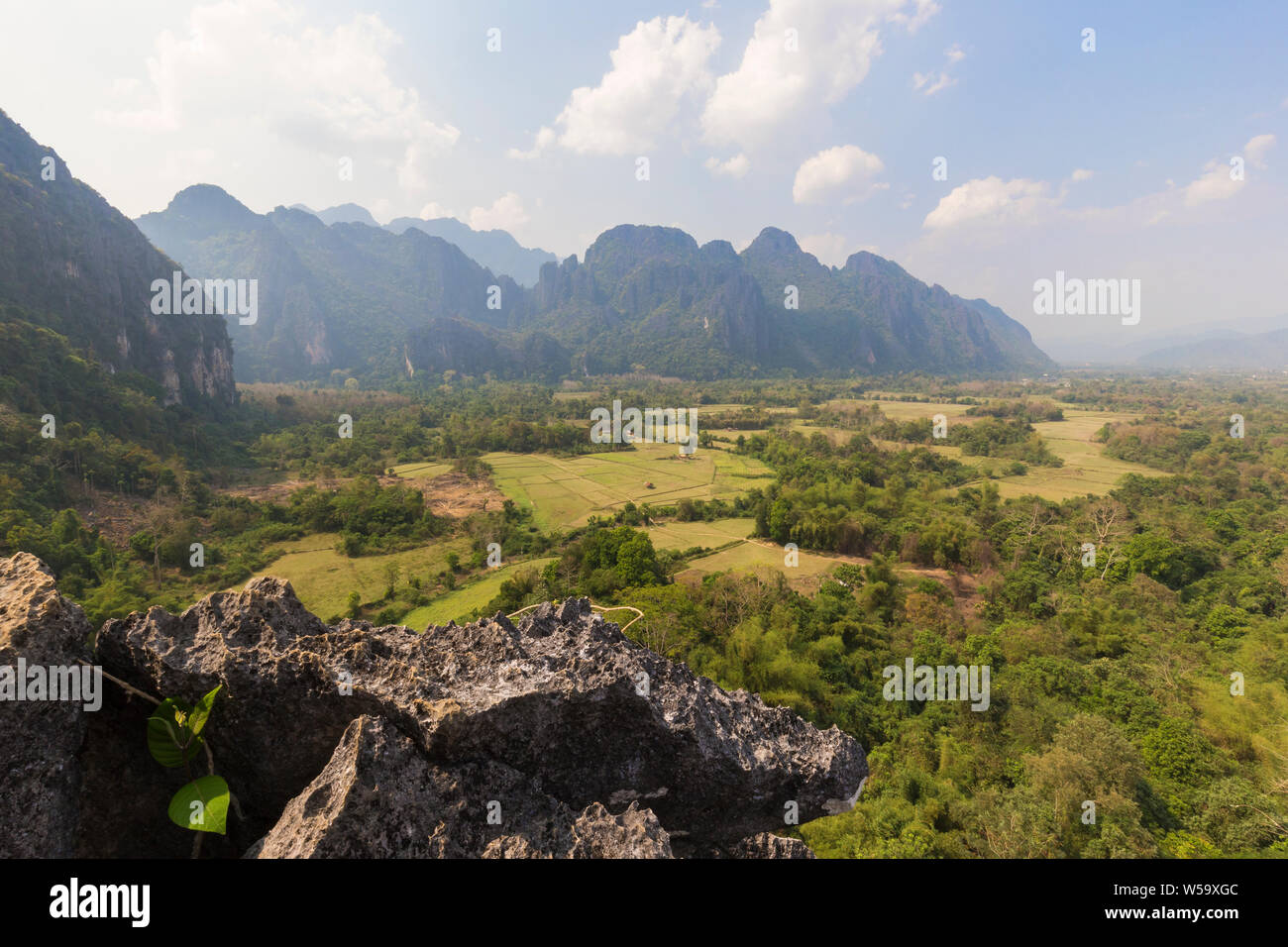 Beautiful view of fields and karst limestone mountains from above near Vang Vieng, Vientiane Province, Laos, on a sunny day. Stock Photo