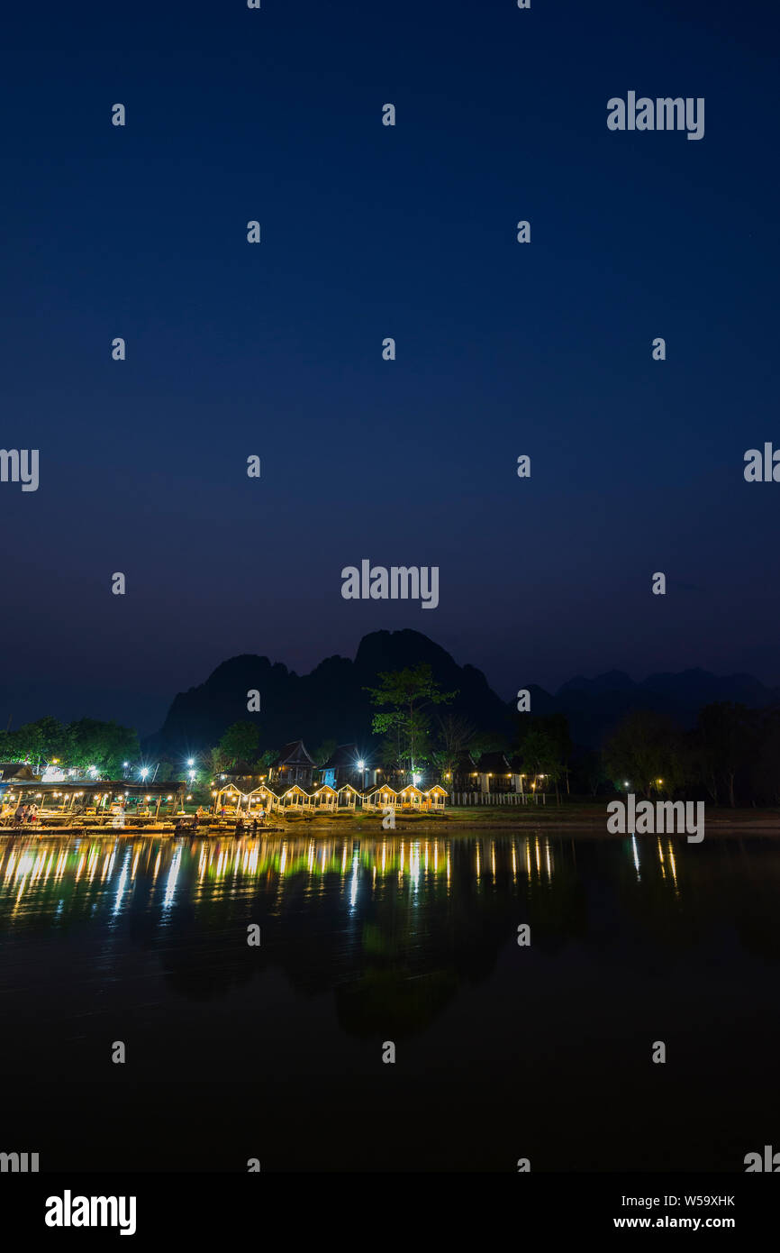 Few people sitting at a lit waterfront restaurant by the the Nam Song River and silhouette of karst limestone mountains in Vang Vieng, Laos, at dusk. Stock Photo