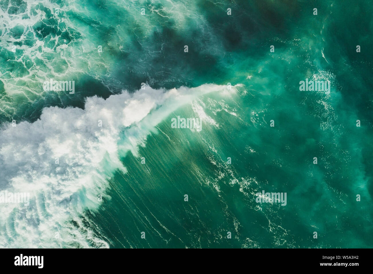 Aerial wave background. Drone shot directly from above, green turquoise color, huge waves. Empty space Stock Photo
