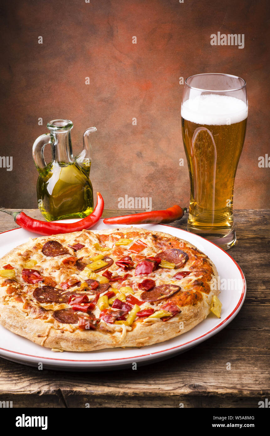 on the rustic wooden table a pizza stuffed with salami and hot pepper and a glass of beer Stock Photo