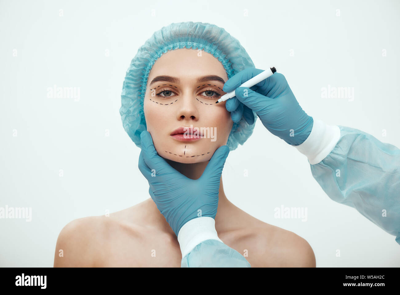 Perfect face. Beautiful and young woman in blue medical hat waiting for facial surgery while plastic surgeon in blue gloves drawing dashed lines on her face. Beauty concept. Facelift. Plastic surgery Stock Photo