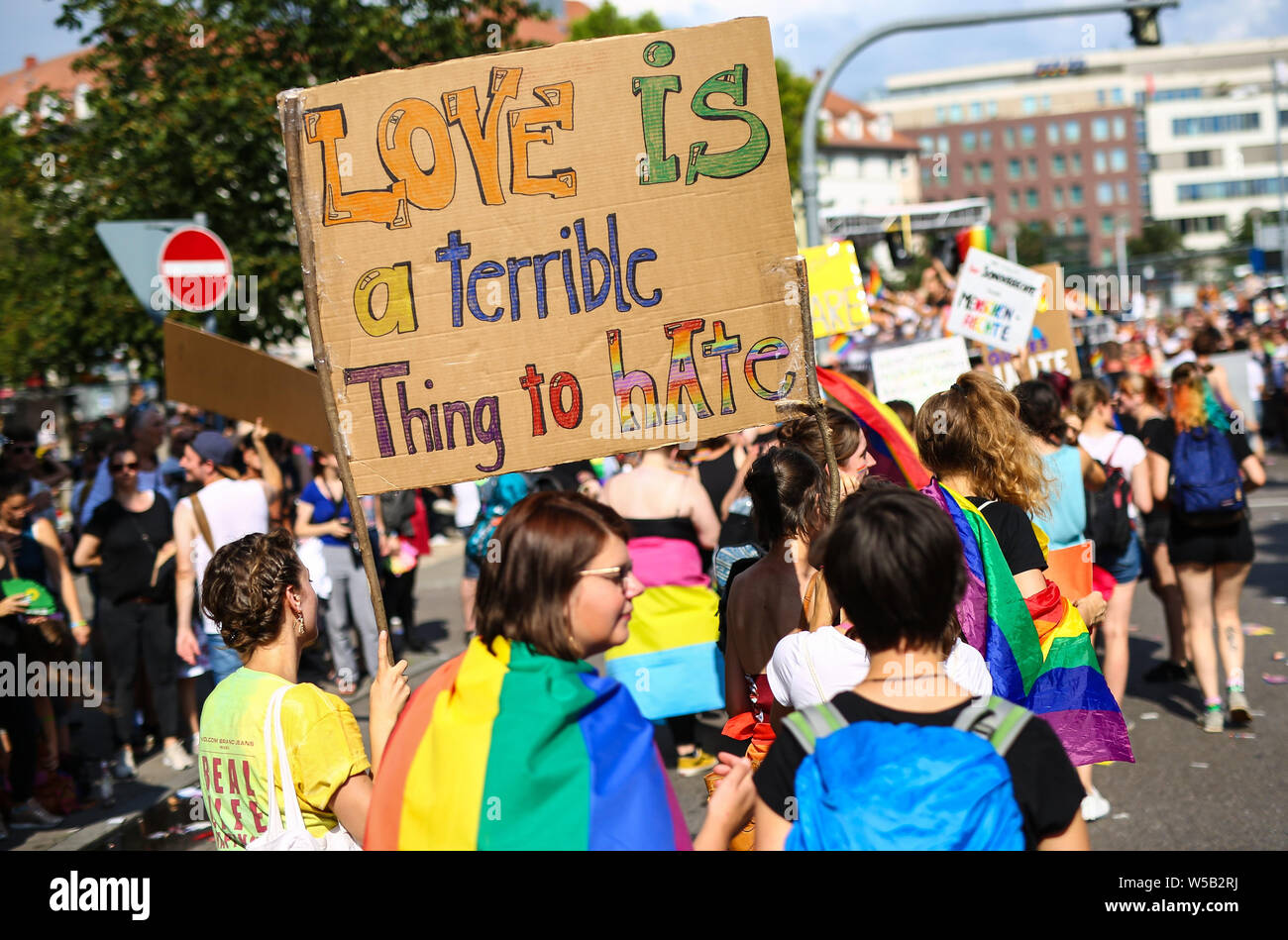 "Stuttgart, Germany. 27th July, 2019. Participants of the Christopher Street Day (CSD) parade walk through downtown and hold a poster with the inscription ""Love is a terrible thing to hate"". The political parade stands for the rights of gays, lesbians, bisexuals and transgender people under the motto ""Courage to Freedom"". Credit: Christoph Schmidt/dpa/Alamy Live News Stock Photo"