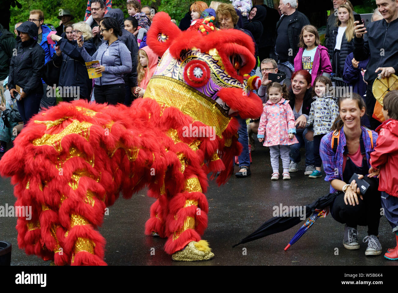 Red Chinese Dragon performing in front of a crowd of people at The Valley Gardens Carnival, Valley Gardens, Harrogate, North Yorkshire, England, UK Stock Photo