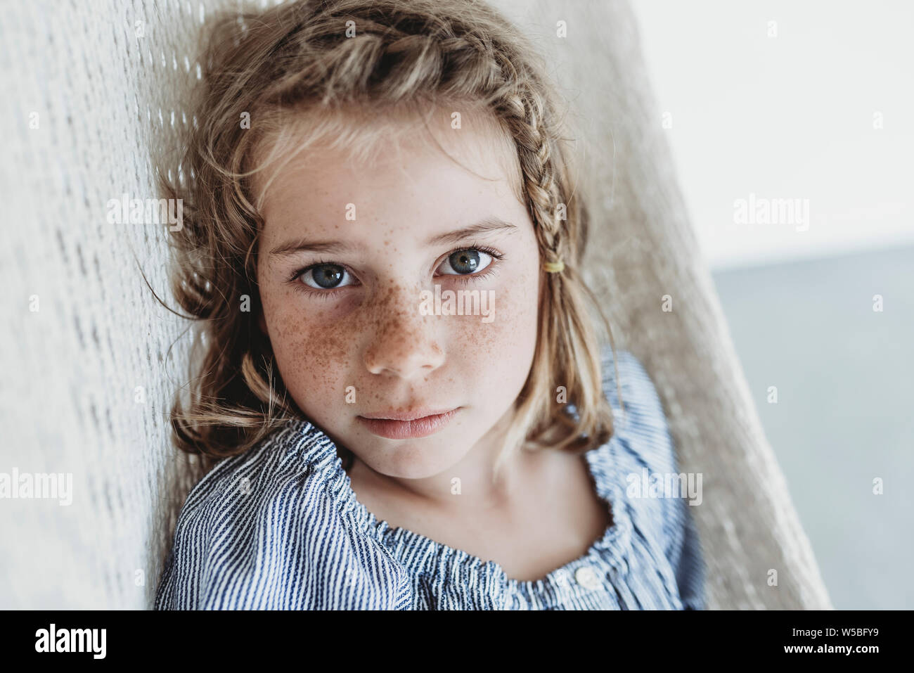 Portrait of serious school-aged girl with braid in her hair Stock Photo