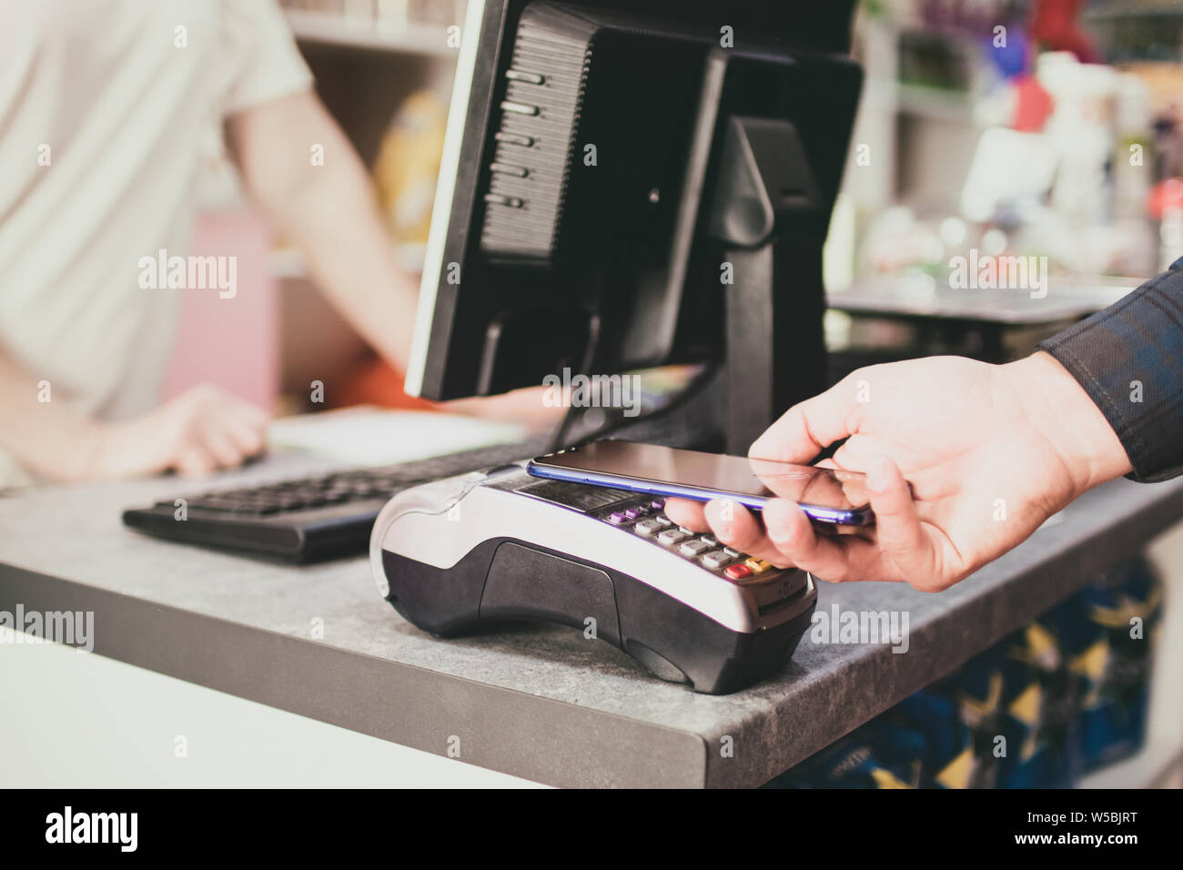 Shopper does payment using smartphone. NFC technology in people life Stock Photo
