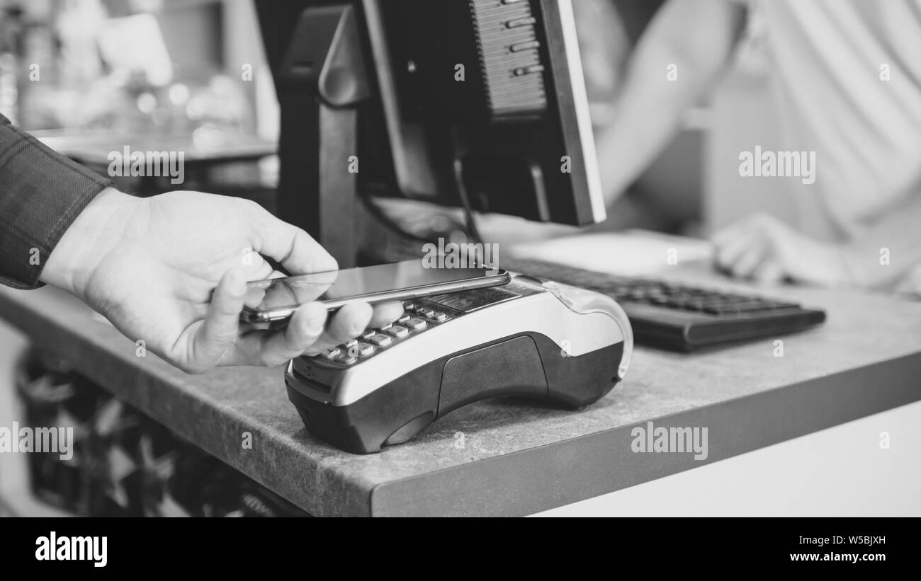 Shopper does payment using smartphone. NFC technology in the store Stock Photo