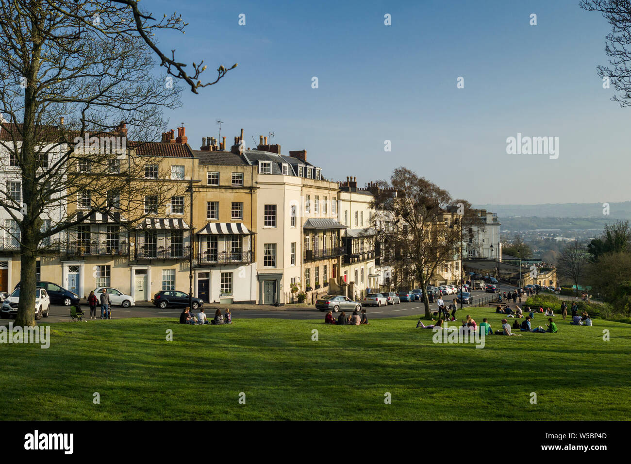 People relaxing and enjoying the green space of SIon Hill alongside Clifton Suspension Bridge and the Georgian properties of Clifton village, Bristol, Stock Photo