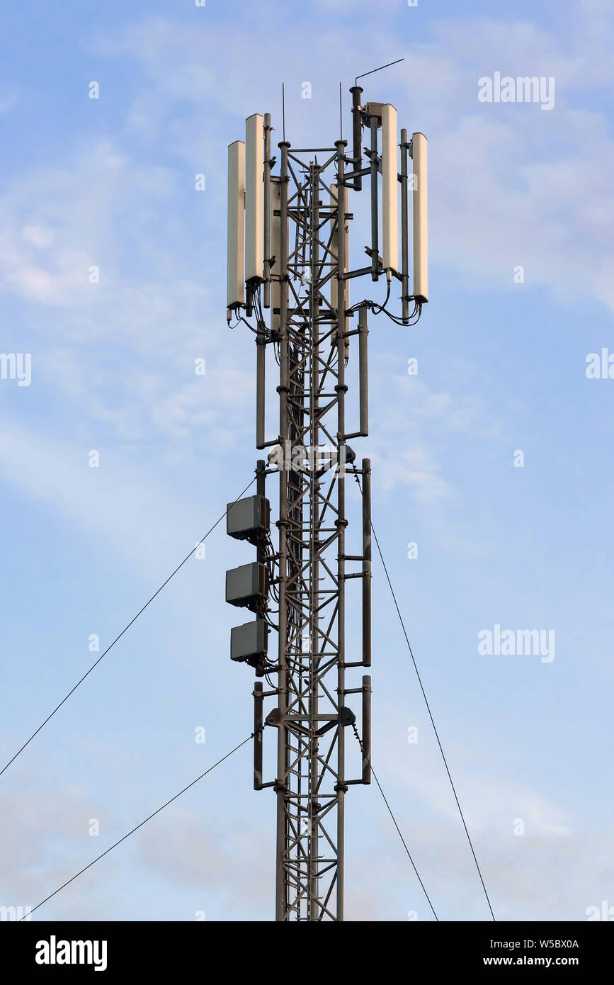 Cellular base station with panel antennas against blue sky Stock Photo