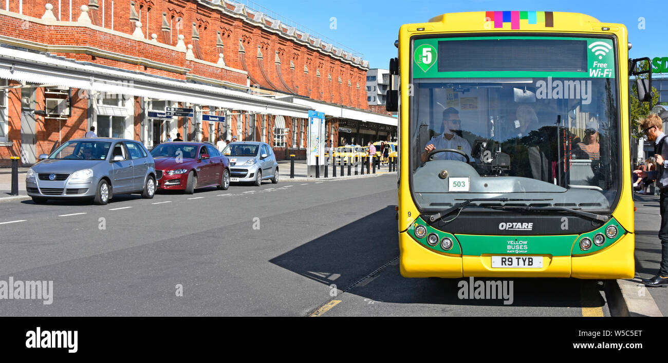 Passengers boarding Yellow buses Optare single decker public transport bus service at stop outside Bournemouth train railway station Dorset England UK Stock Photo