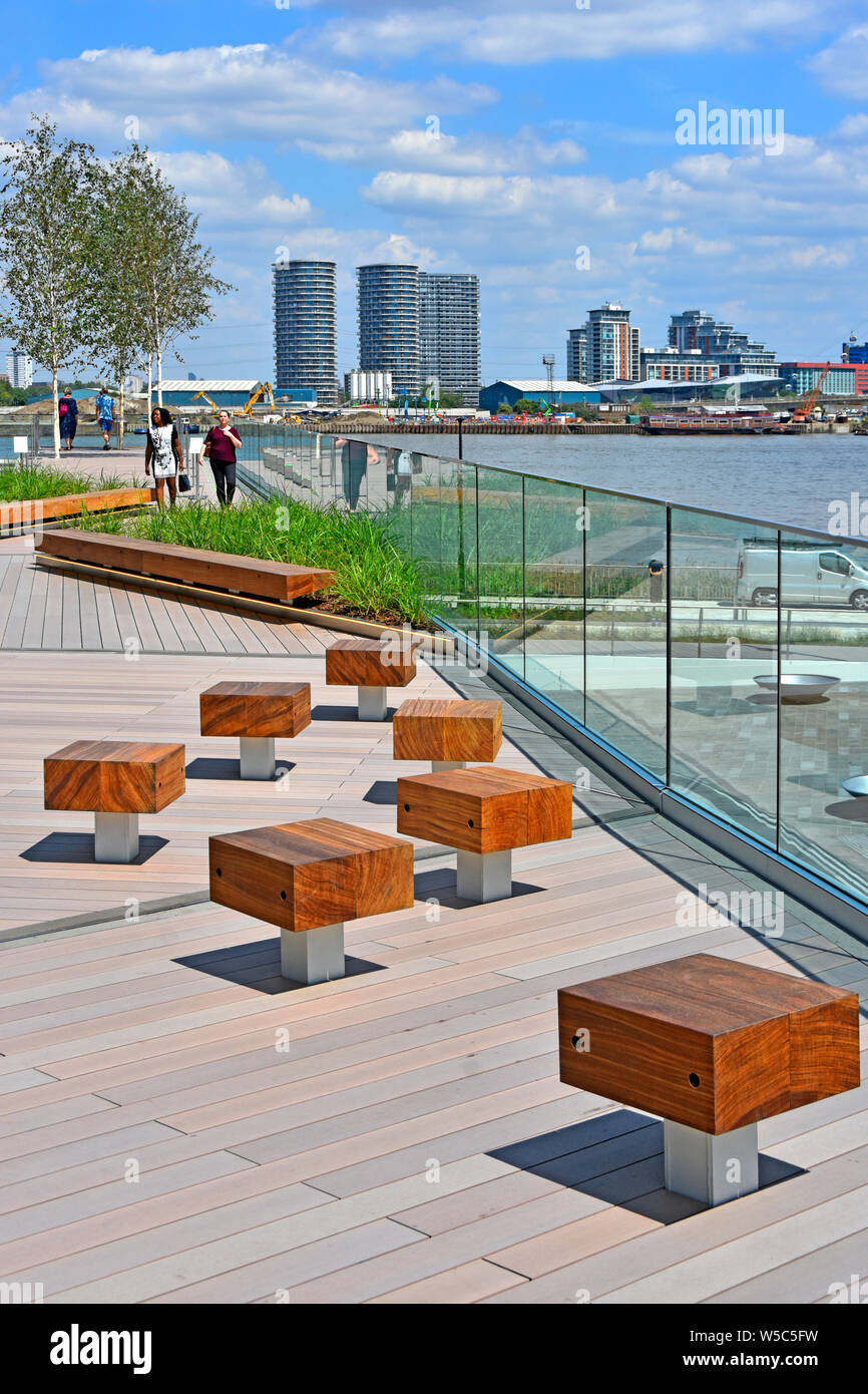 Wood seats on 'The Tide' bridges a linear park links River Thames riverside with high line walks around Greenwich Peninsula South London England UK Stock Photo