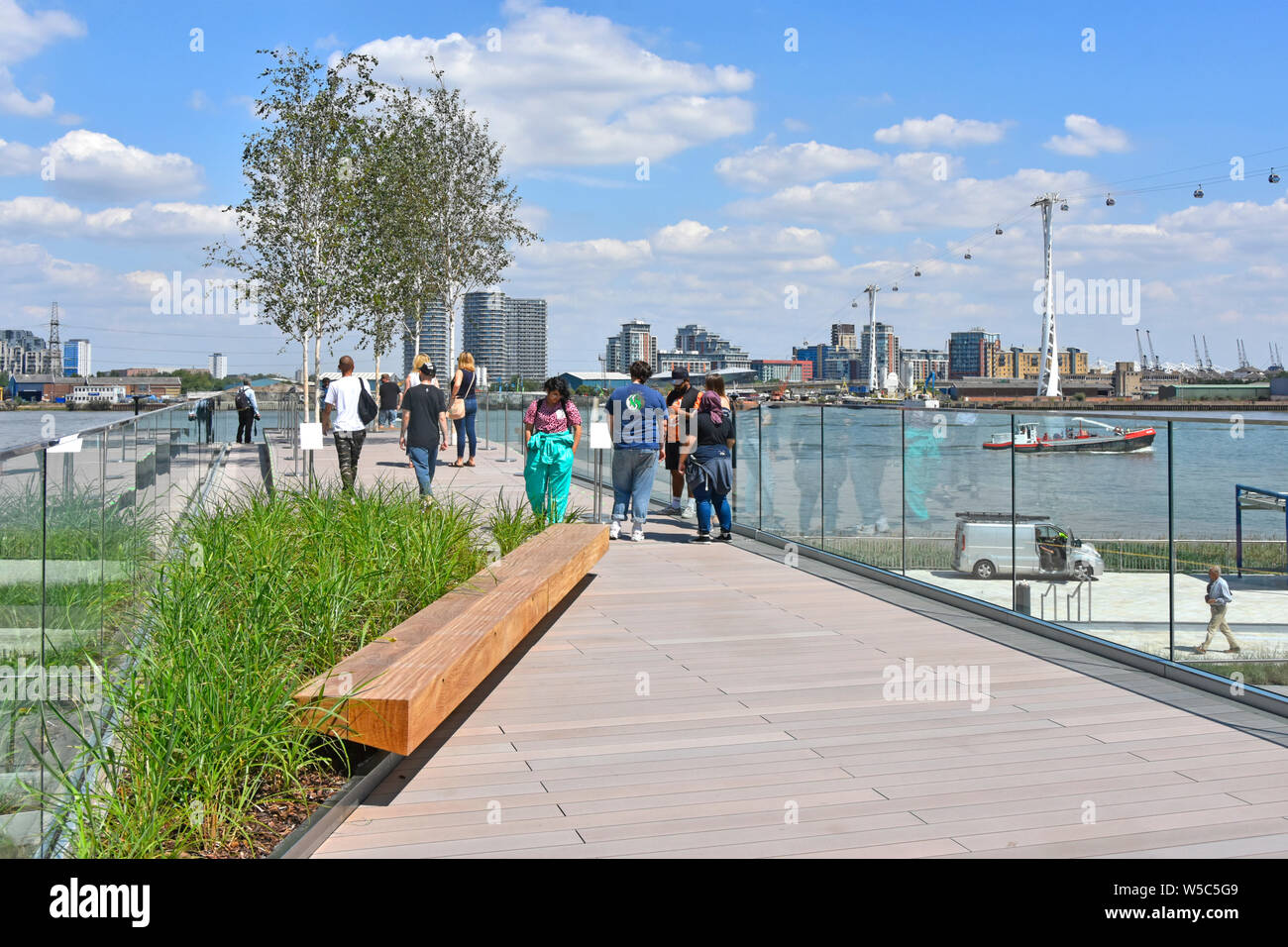 People walking The Tide bridges a linear parks links River Thames riverside with elevated walks around the Greenwich Peninsula South London England UK Stock Photo