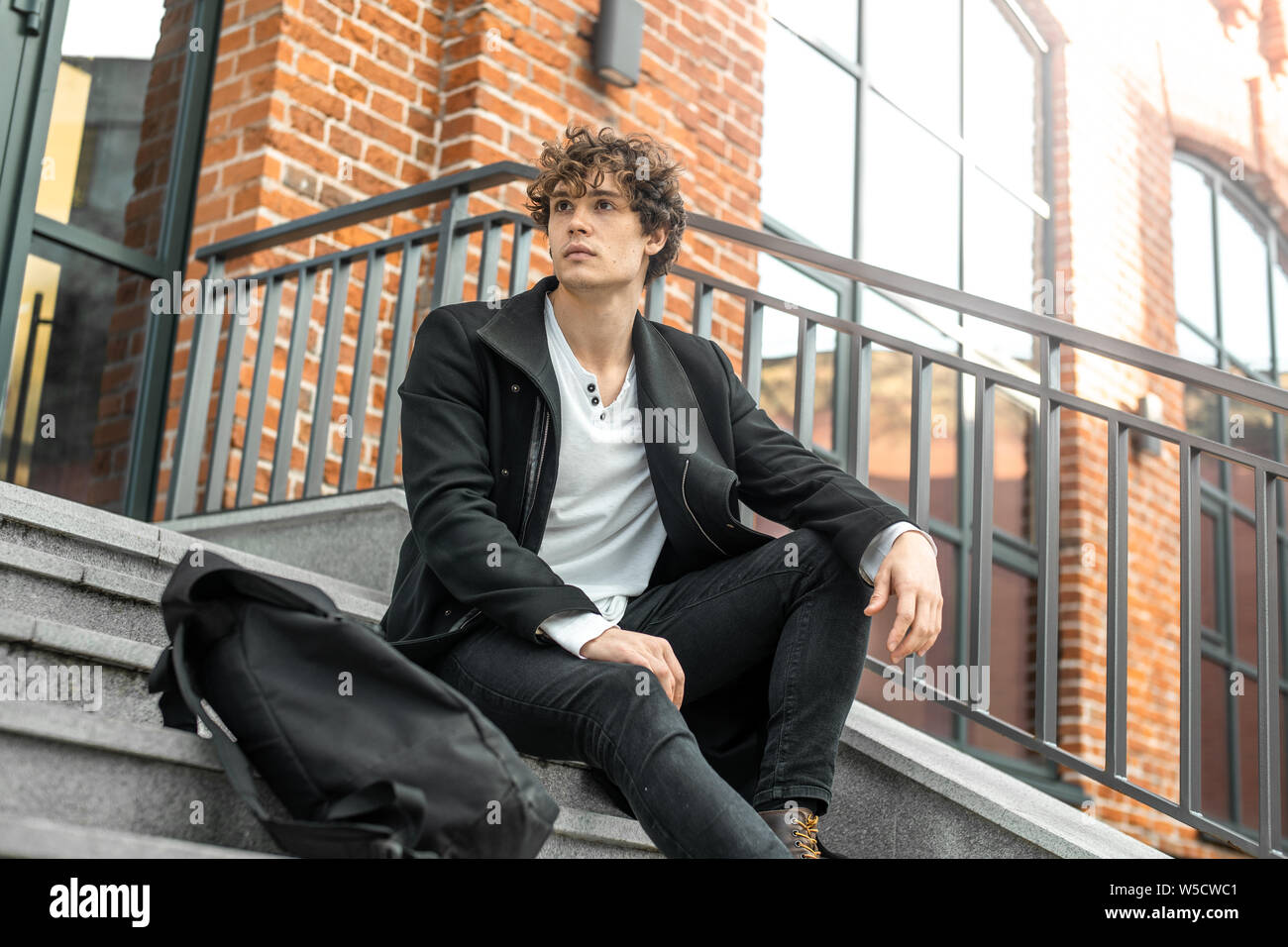 Young attractive pensive man sitting on concrete steps of modern red bricked building. Stock Photo