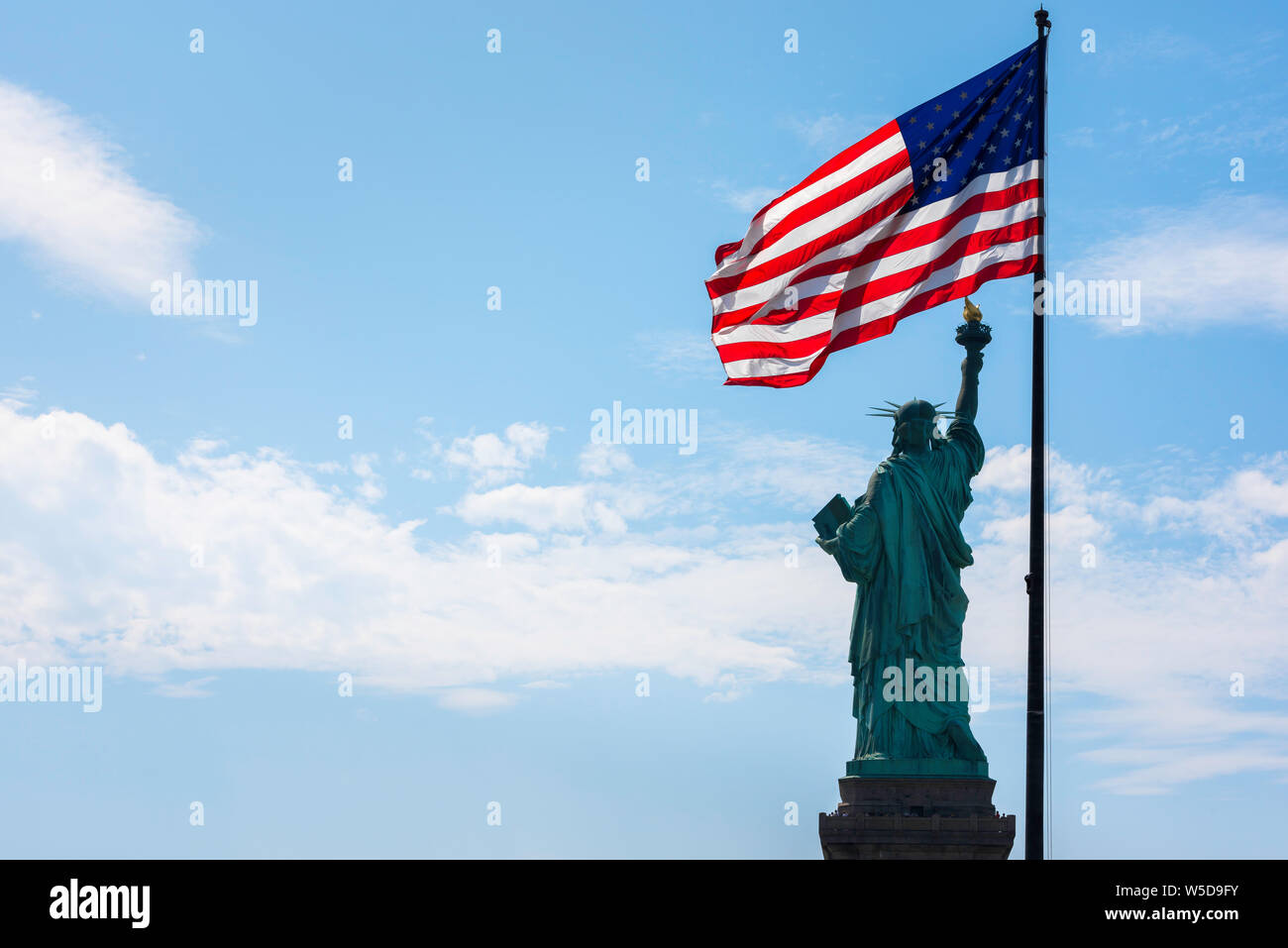 Freedom, view of the rear of the Statue of Liberty and a back-lit stars and stripes flag with copy space sited left, New York City, USA. Stock Photo