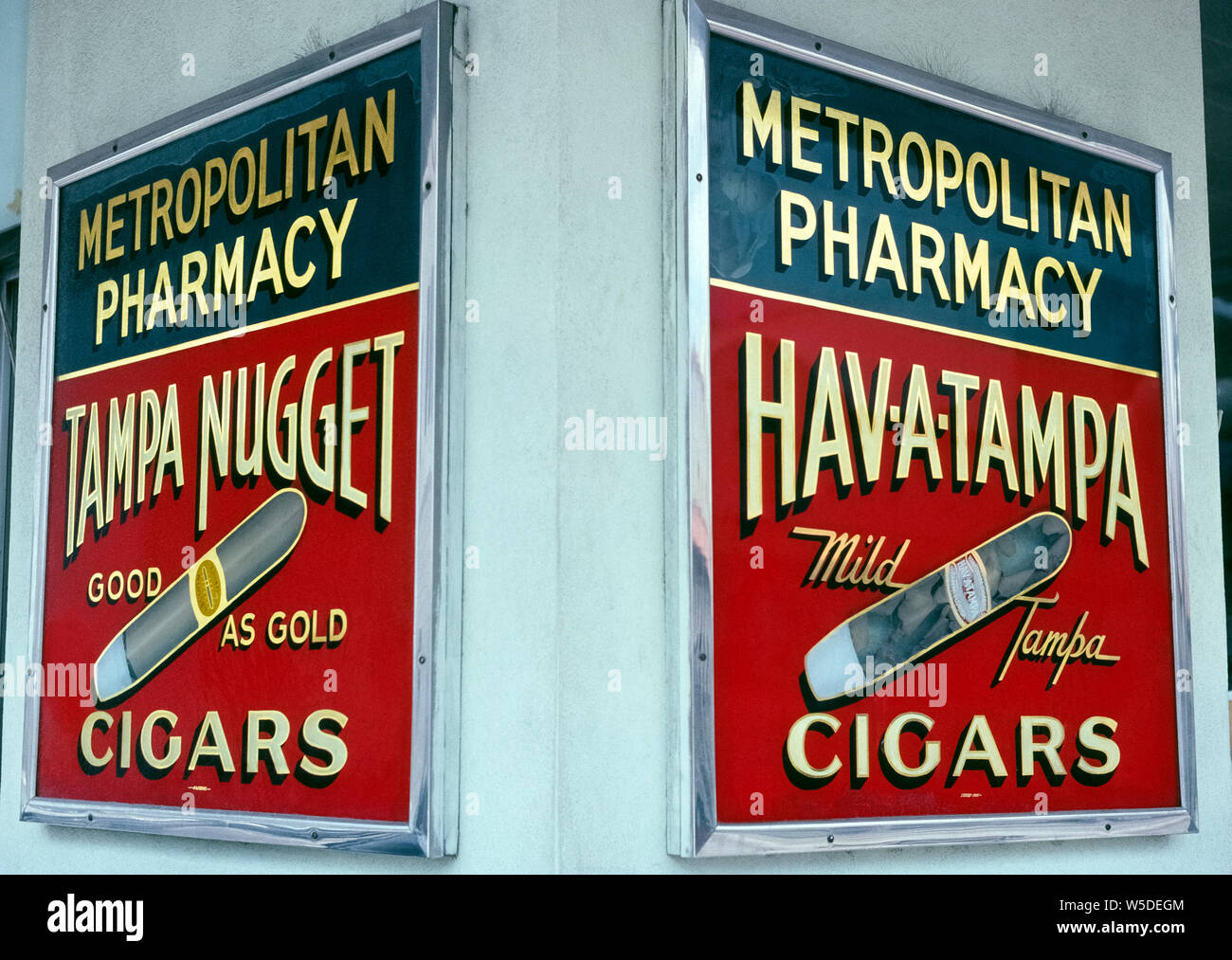 Two vintage storefront signs advertise Tampa cigars that were made in Ybor City, a National Historic Landmark District in Tampa, Florida, USA, once known as the cigar capital of the world. Tampa Nugget and Hav-A-Tampa cigars were manufactured there by the Hav-A-Tampa Cigar Company from 1902 until 2009 when production was moved to Puerto Rico. Currently Hav-A-Tampa is known for its top-selling slender cigars with wood tips, named Jewels, which are offered in flavors called Original, Sweet, and Vanilla. Historical photograph. Stock Photo