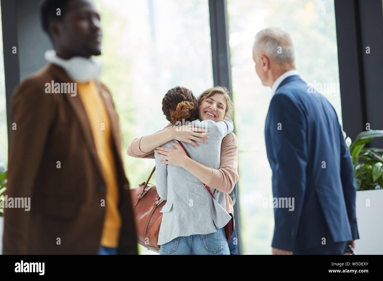 Happy excited young friends standing in hall and hugging in airport after long separation Stock Photo