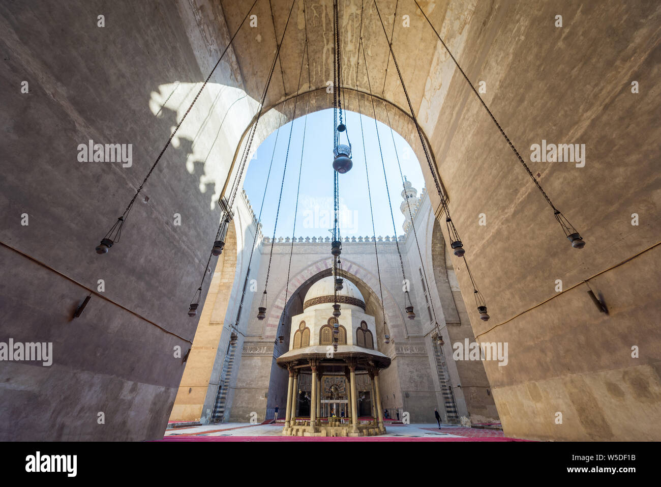 Cairo, Egypt - December 16, 2017: Courtyard of the Mosque of Sultan Hasan with Ablution fountain and huge arch, and few tourists visiting the place at the early morning Stock Photo