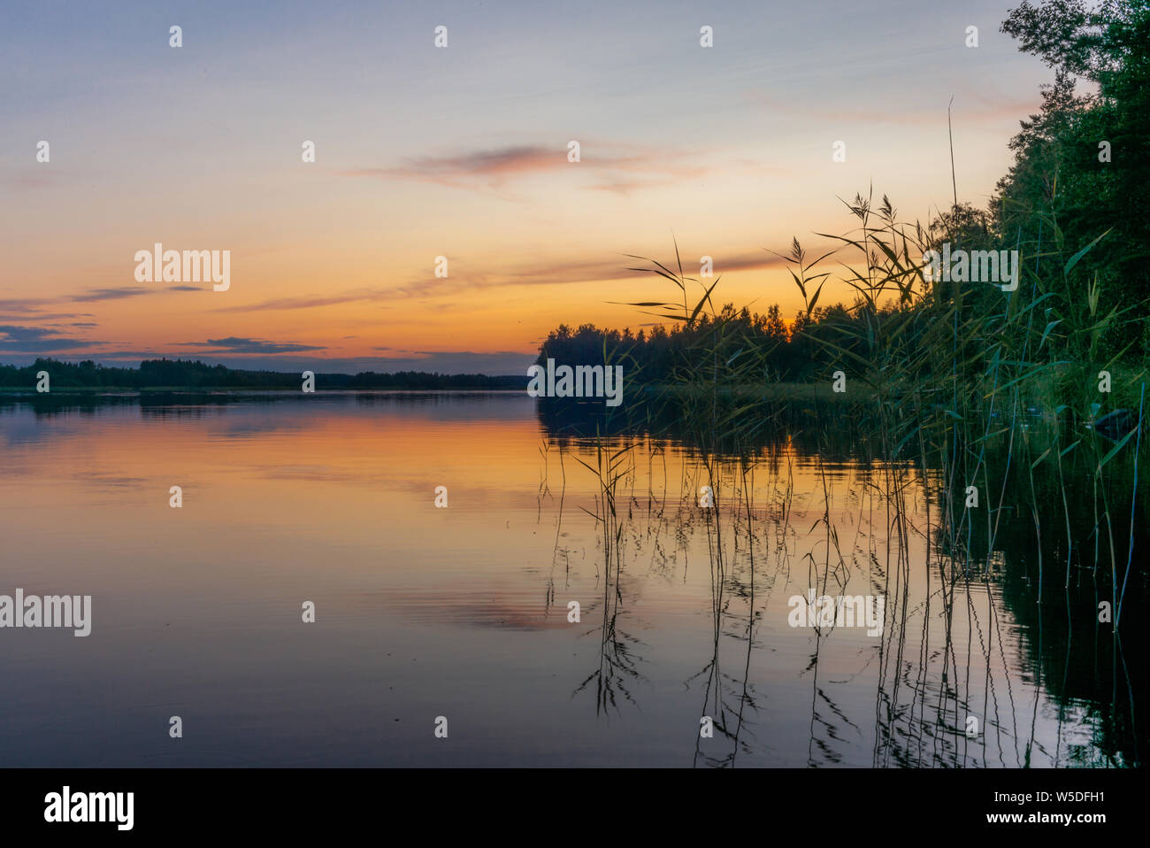 Reflections on the calm waters of the Saimaa lake in Finland at Sunset  - 5 Stock Photo