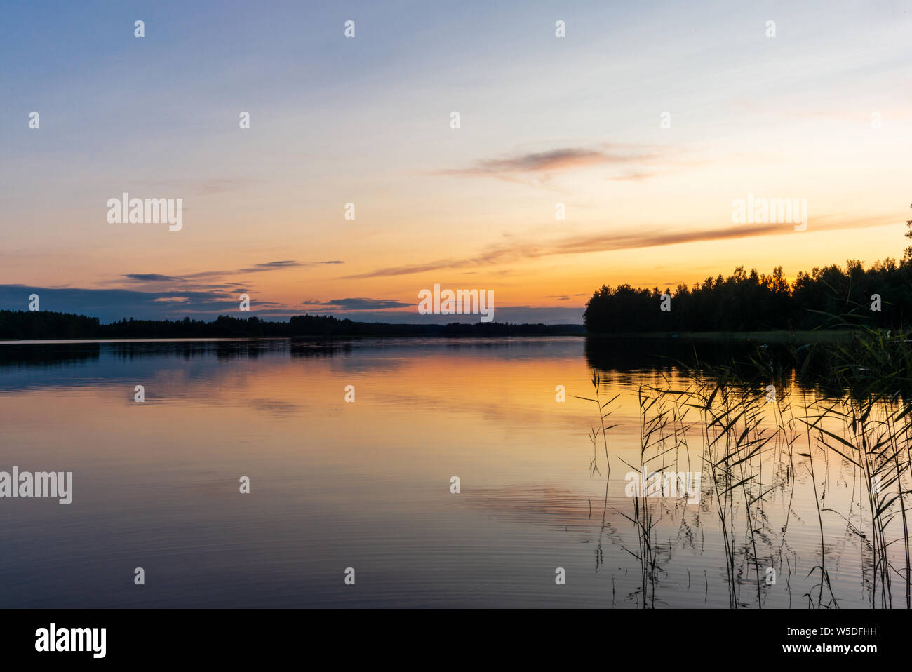 Reflections on the calm waters of the Saimaa lake in Finland at Sunset  - 2 Stock Photo
