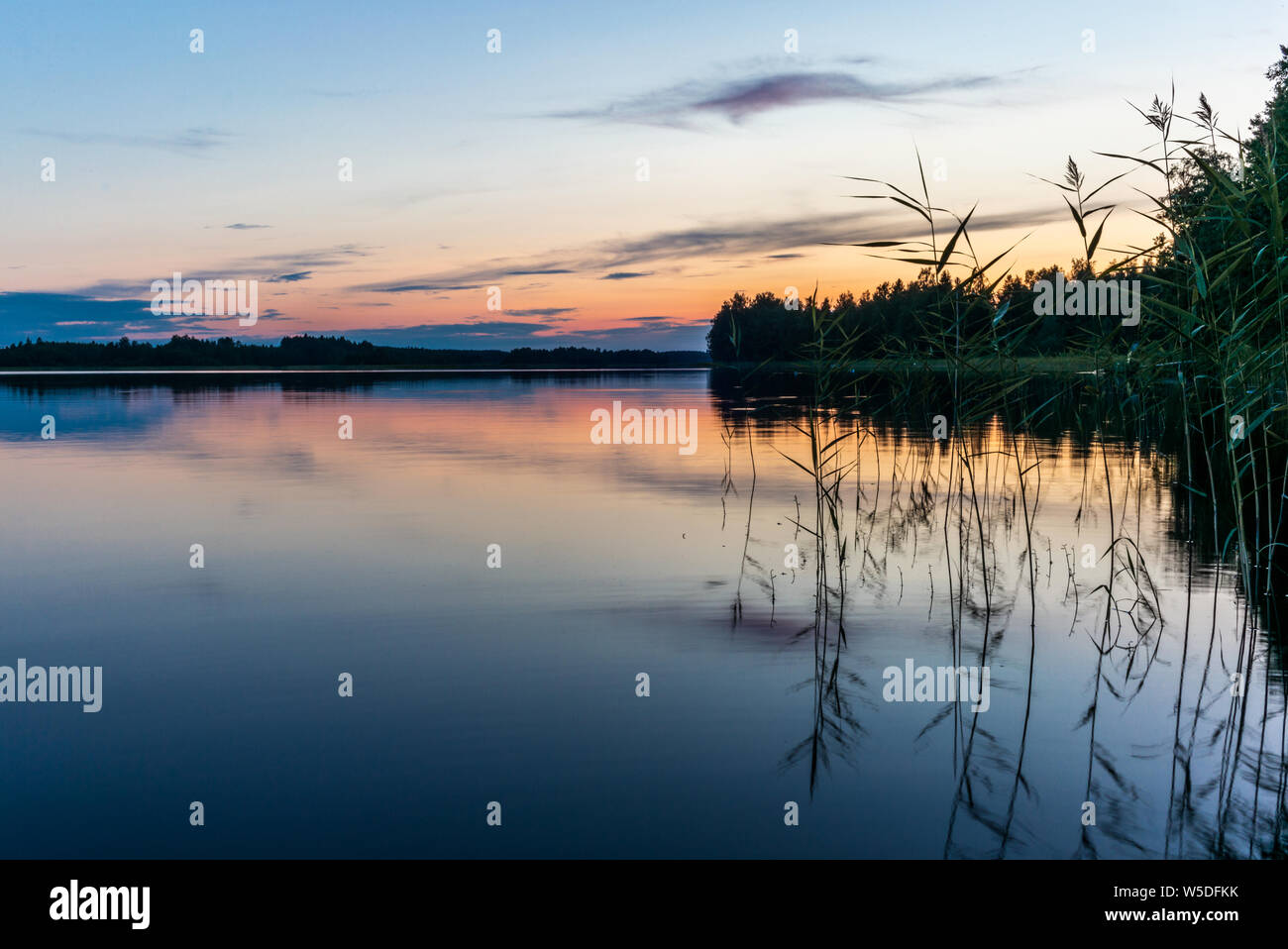 Reflections on the calm waters of the Saimaa lake in Finland at Sunset  - 9 Stock Photo